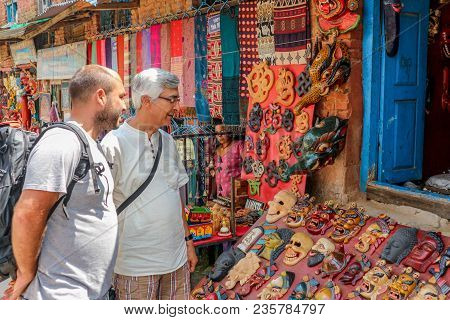 Kathmandu, Nepal - September 22, 2016: Tourist Men Looking At Some Souvenirs In Front Of A Shop In K