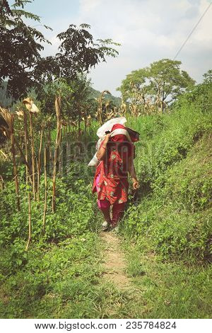 Kathmandu, Nepal - September 22, 2016: Nepalese Woman In Traditional Clothes Carrying Heavy Load On