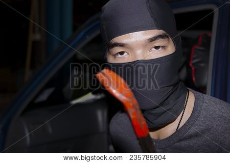 Masked Thief With Balaclava Holding Crowbar To Breaking Into A Car. Crime Concept