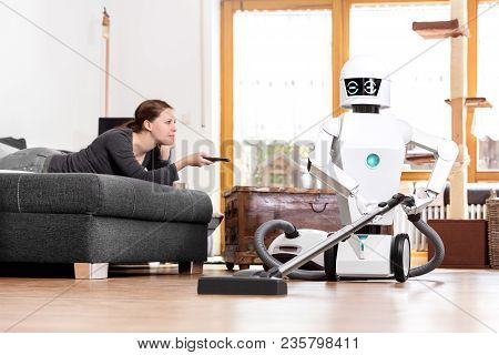 Woman Is Enjoying Her Leisure While A Robot Is Doing The Work In The Household. Aai Is Vacuuming The