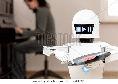 Music Entertainment Service Robot Is Playing Music Files While A Man In The Background Is Playing A