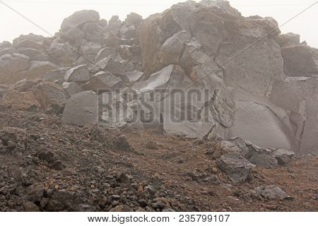 The Etna Volcano. The Etna Volcano Crater. Black Volcanic Earth, Volcanic Lava And Stones.  Dense Fo
