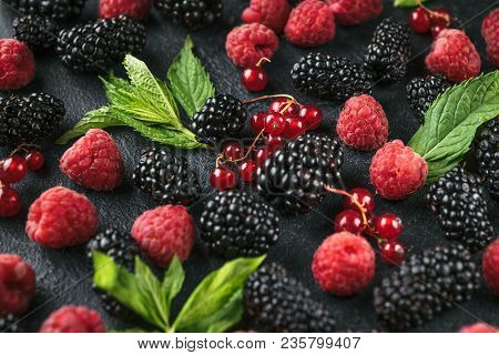 Close-up Photo Of Ripe Berries Of Blackberry, Raspberry And Currant And Green Mint Leaves On A Black