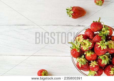 Top View Photo Of A Glass Plate With Ripe Red Strawberries On A White Wooden Table. Four Strawberrie