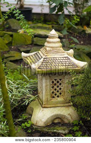 Decorative Garden Lantern Toro In Japanese Style On The Background Of Garden Vegetation