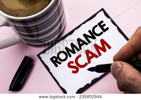 Handwriting text writing Romance Scam. Concept meaning Dating Cheat Love Embarrassed Fraud Cyber Couple Affair written by Man Sticky Note paper holding Marker plain background Coffee Cup poster