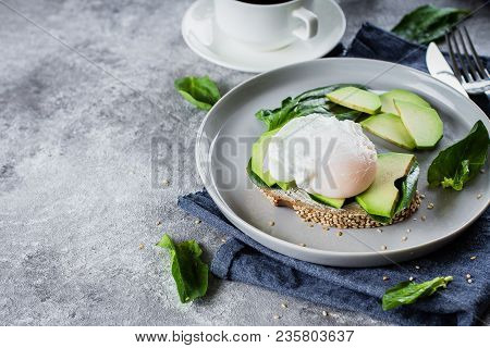 Sandwich With Avocado, Spinach And Poached Egg On Whole Wheat Bread On Plate On Stone Background. He