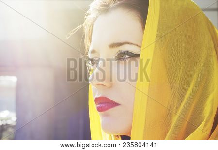 Pensive Beautiful Girl In A Yellow Scarf Looking Into The Distance