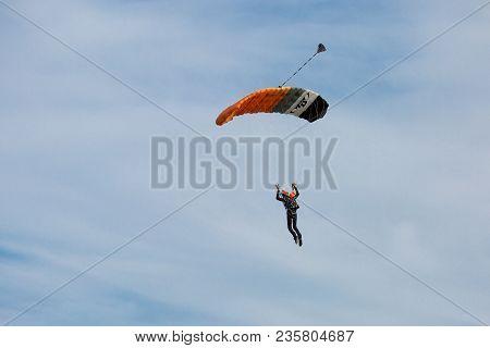Reggio Emilia, Italy - May 2017:  Parachutist With Orange Parachute Against Blue Sky Preparing For L