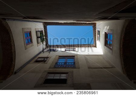 Straight Up View Of The Blue Sky From Under An Ancient Archway. Alfama Disctrict, The Most Famous An