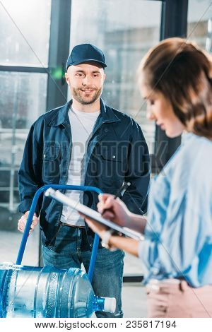Woman Signing Cargo Declaration While Water Delivery Courier Waiting