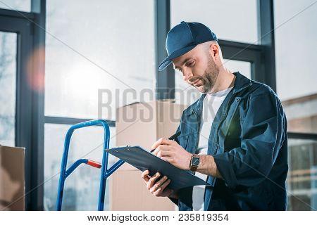 Loader Man Filling Cargo Declaration By Stacks Boxes