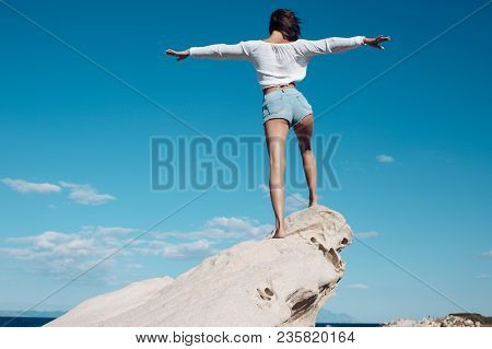 Girl Enjoys Freedom On Windy Day, Put Hands At Sides. Lady Stands On Stone Or Reef In Sea. Vacation