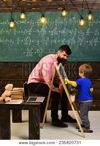 Tutor Explaining Math To Little Kid. Turned Back Boy Wiping Chalkboard With Yellow Cloth. Daddy Sitt