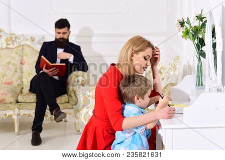Home Schooling Concept. Father Reading Book, While Mother Teaches Son Preschooler To Draw Or Write,