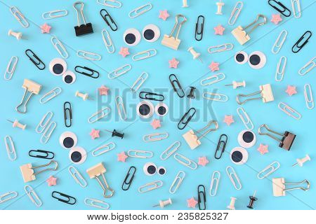 White And Black Paper Clips, Pink Stars And Stationery Are Scattered Chaotically On A Blue Backgroun