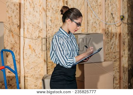 View Of Businesswoman With Clipboard Filling Cargo Declaration