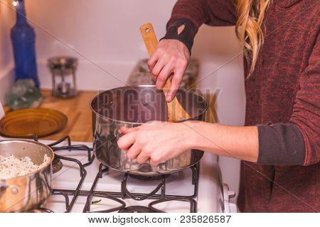 Woman Cooking Food In Stainless Steel Pot On Gas Stovetop.