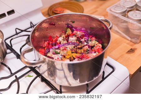 Vibrant Vegetables With Spices Cooking In Stainless Steel Pot On Gas Stovetop.