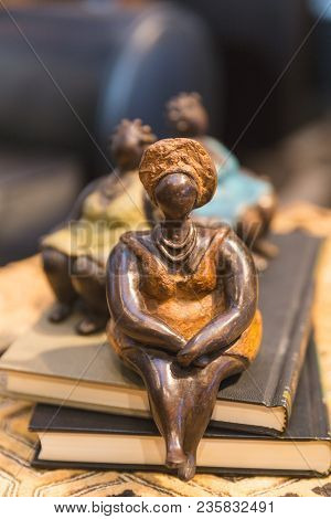 Sculptures Of African Women In Traditional Clothing.
