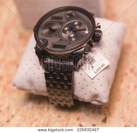 Gray Or Silver Metal Watch Wrapped Around Cushion With Price Tag Reading