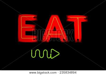 A Neon Sign With The Word Eat And An Arrow Pointing The Direction.