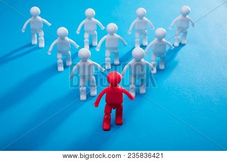 Red Human Figure Leading Team Toward Success On Blue Background