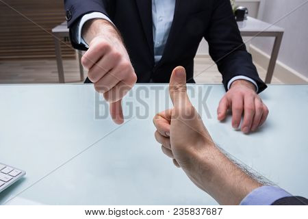 Two Businesspeople Showing Thumb Up And Thumb Down Sign Over Desk In Office