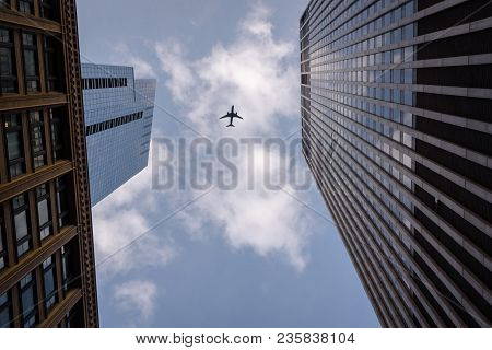 Airplane Flying Overhead In Downtown Chicago In The Middle Of Two Buildings