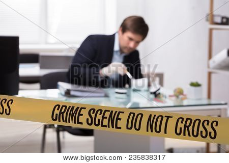 Forensic Expert Searching For Crime Evidence On Pencil Holder Behind Crime Scene Tape