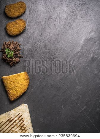 Fast Food Composition With French Tacos, Cordon Bleu, Nuggets And Beef On Slate