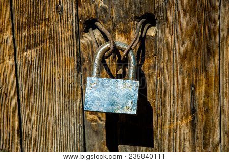Rusty Padlock On An Old And Deteriorated Door