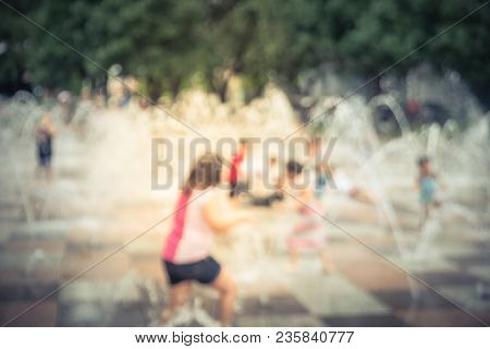 Blurred Motion Kids Having Fun At Green Playground In Summer Time