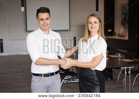 Portrait Of Successful Partners Shaking Hands In Boardroom. Young Caucasian Businessman Congratulati