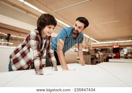 Tidy Bearded Father With Young Son Is Testing Mattress For Softness. Testing Softness Of Mattress. C