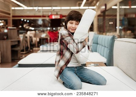 Joyful Boy Enjoying Softness Of Orthopedic Pillow Rejoices In Furniture Store. Joyful Little Boy Hug
