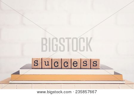 The Word Success, Alphabet On Wooden Cubes On Top Of Books. Background Copy Space, Vintage Minimal.