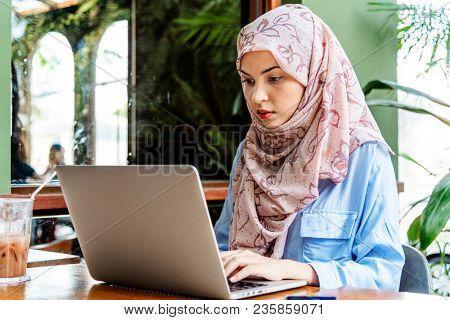 Islamic woman working on laptop