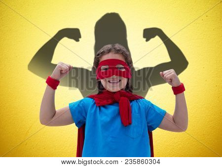 happy girl dressing up like a superwoman in front of fists draw on yellow wall