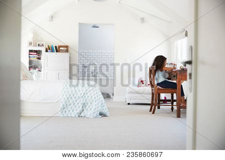 Young black girl sitting at desk, doing homework in her room