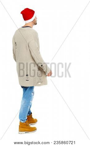 Back view of a man in a Christmas hat. Rear view people collection.  backside view of person.  Isolated over white background.  Side view of a guy in New Year's clothes