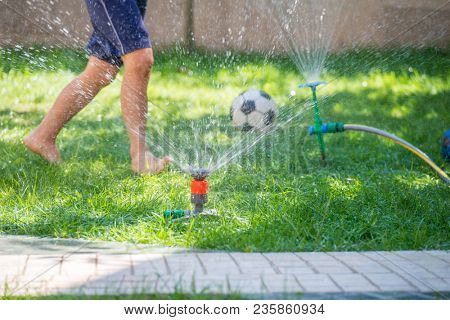 Happy boy playing with water sprinkler