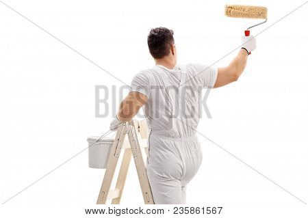 Rear view shot of a painter climbed up a ladder painting with a roller isolated on white background