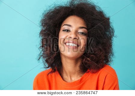 Happy brunette woman in orange shirt looking on camera with perfect smile isolated over blue background