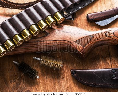 Hunting equipment - pump action shotgun, 12 guage cartridge and hunting knife on the wooden table.