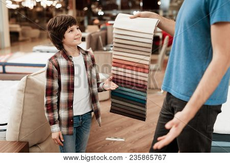 Man With Young Boy Chooses Color On Color Palette. Selecting Color Of Mattress On Color Palette Guid