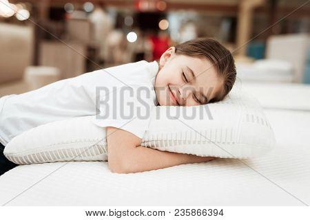Nice Little Girl Hugs Pillow In Store Of Orthopedic Mattresses. Testing Softness Of Pillow. Check So