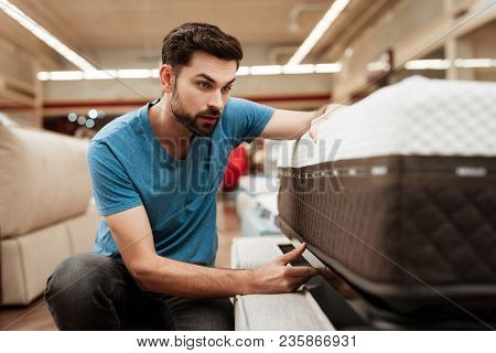 Handsome Bearded Man Is Testing Mattress In Furniture Store. Orthopedic Mattress For A Healthy Postu