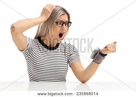 Shocked young woman sitting at a table and measuring her blood pressure isolated on white background