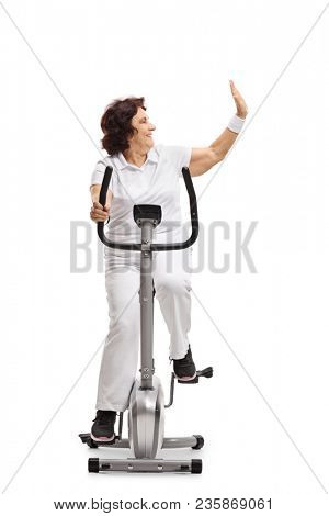 Elderly woman exercising on a stationary bike and making a high-five gesture isolated on white background poster